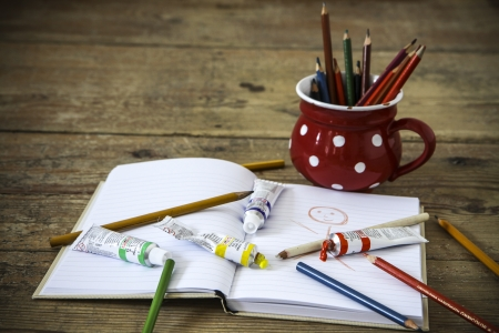 vintage crayons in the red cup with notebook on the wood floor