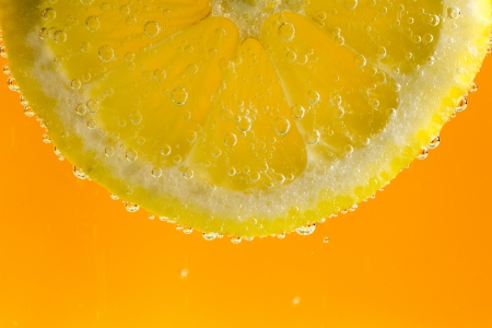 Beautiful fresh slice of lemon in the water with bubbles
