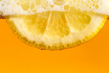 Beautiful fresh slice of lemon in the beer with bubbles photo