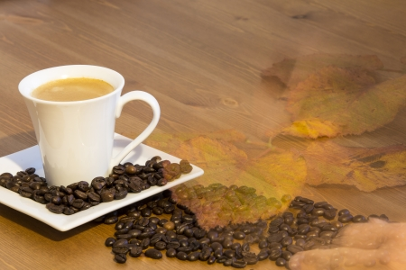 Coffee cup and saucer on a wooden table with leaf photo