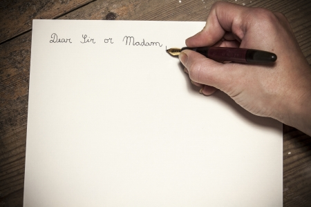 Old fashioned letter with a pen in a hand photo