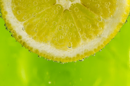 Beautiful fresh slice of lemon in the water with bubbles photo