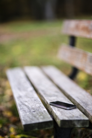 found: Someone forgot cell phone on a bench in the park Stock Photo