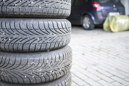 car tires prepared to replace in a garage with car in background photo