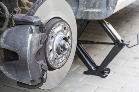 Repairing brakes or changing tires on car photo