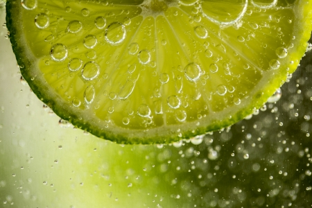 Beautiful fresh slice of lime in the water with bubbles