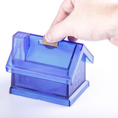 Blue House Money Box on White Background with man hand and coin photo