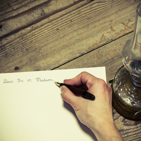 Writing on an Old fashioned letter with a pen and lamp photo