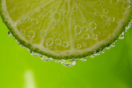 Beautiful fresh slice of lime in the water with bubbles photo