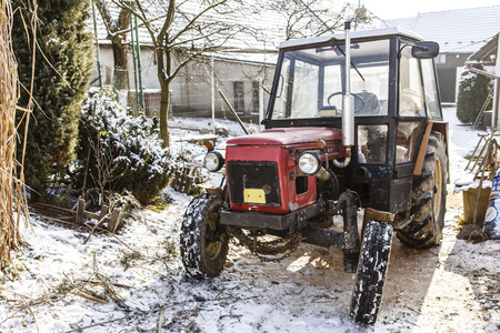 Old red Czech tractor on the snow - in the yard and winter