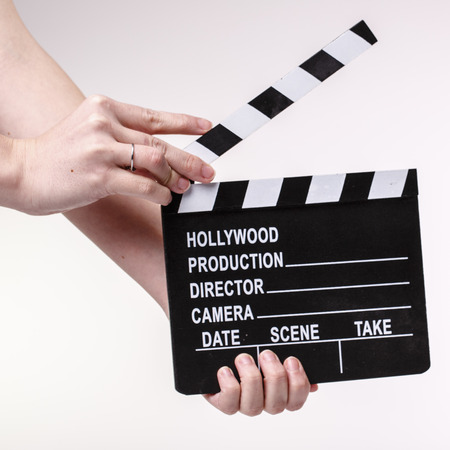 Film or Movie flapper in woman´s hands on white background