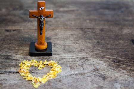 Beautiful old cross with jesus and yellow heart from leafs on the old wooden floor photo