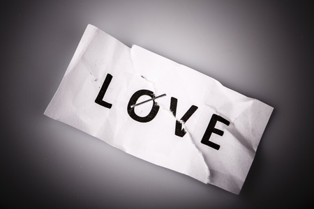 stapled: Love word written on torn and stapled paper on white Stock Photo
