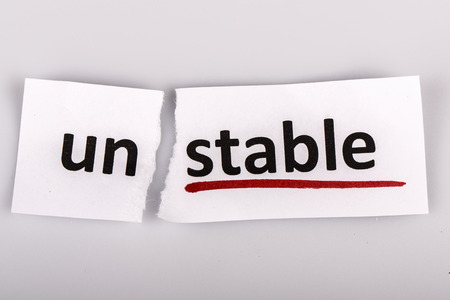 The word stable changed to unstable on torn paper and white background Reklamní fotografie