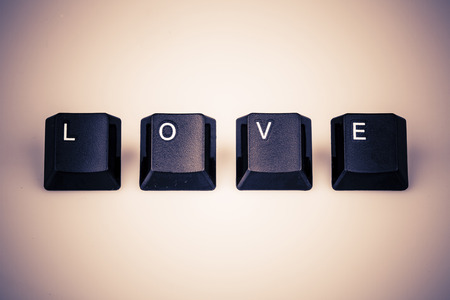 Word love formed with computer keyboard keys on white background with shadow photo