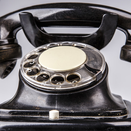 Old black phone with dust and scratches, isolated on white background - retro photo