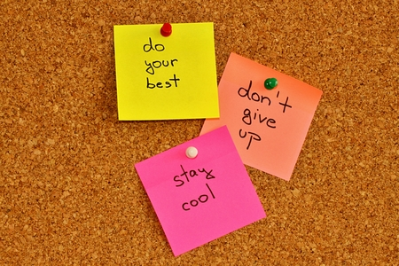not give: Cork notice board with three colourful sticky note pads Stock Photo