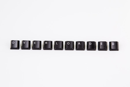 overloaded word written with black computer buttons on white background photo