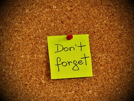 not to forget: Cork notice board with one yellow sticky note pad with text please do not forget