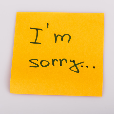 i am sorry: text i am sorry on short orange note paper