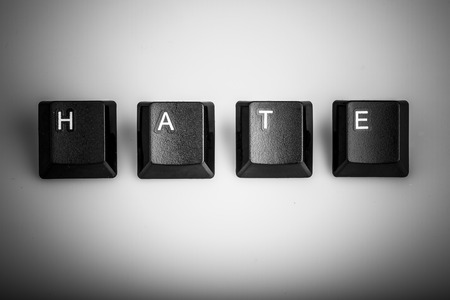 Word hate formed with computer keyboard keys on white background with shadow photo