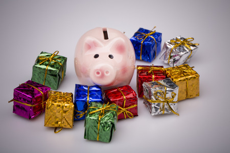 christmas savings: Pig money box between christmas gift on white background Stock Photo