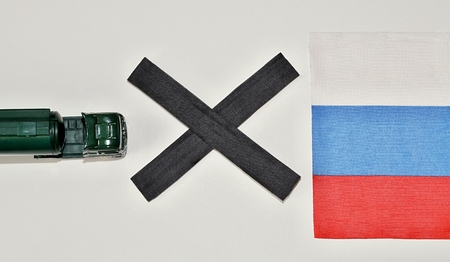 Truck and black in front of a Russian flag simbolize stop of food import to Russia photo