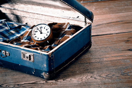 Old suitcase with old alarm clock and old shirt Фото со стока
