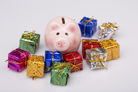 Pig money box between christmas gift on white background photo