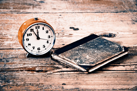 Time to read, old alarm and book on old wood floor photo
