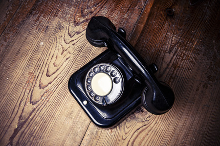 Old black phone with dust and scratches, isolated on wooden retro floor 写真素材