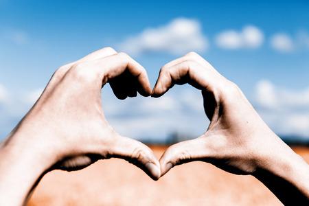 simbolo de la mujer: Forma hermosa manos amor - coraz�n en campo amarillo y el azul cielo Foto de archivo