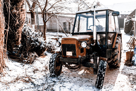 Old red Czech tractor on the snow - in the yard and winter photo
