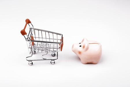 spending money: shopping cart versus pig money box - save money against spending money Stock Photo