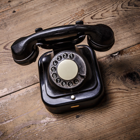 Old black phone with dust and scratches, isolated on wooden retro floor photo