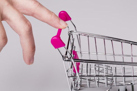 woman shopping cart: beautiful pink shopping cart in woman hand with white background - shopping concept
