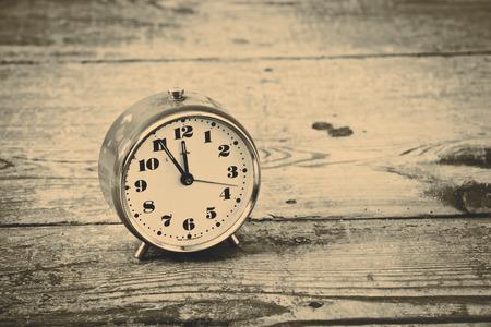 alarmclock: Beautiful old orange alarm clock on the wooden flool Stock Photo