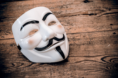 vendetta: white anonymous mask on wood - retro style Editorial