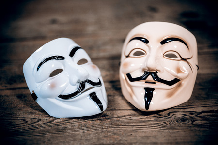 vendetta: white and yellow anonymous masks on wood - retro style Editorial