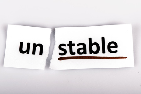 changed: The word stable changed to unstable on torn paper and white background Stock Photo