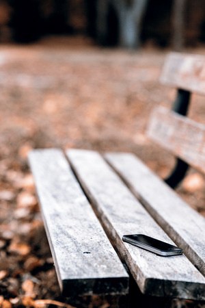 Someone forgot cell phone on a bench in the park Stockfoto