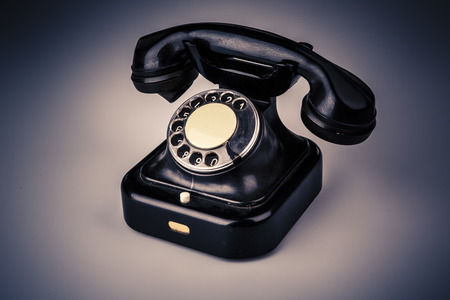 Old black phone with dust and scratches, isolated on white background - retro Фото со стока