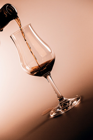 drunks: alcohol drink pouring into glass isolated on white background Stock Photo