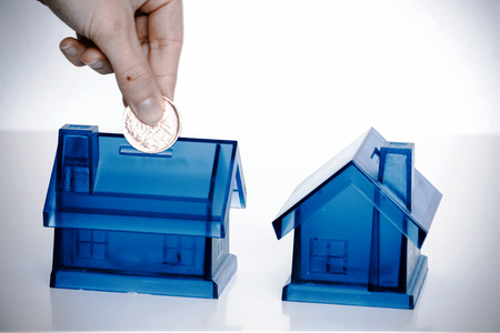 House Blue Money Box on White Background with woman hand with coin Фото со стока