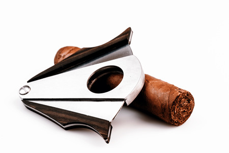 Expensive cigar and cutter on a white background