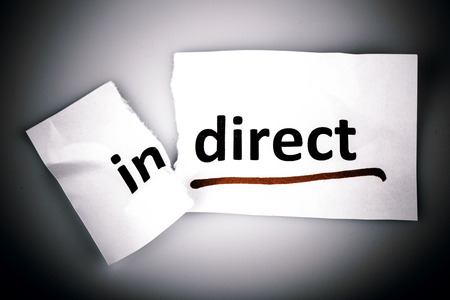 indirect: The word indirect changed to direct on torn paper and white background Stock Photo