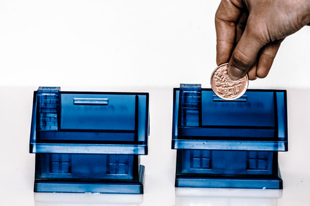 coin box: House Blue Money Box on White Background with woman hand with coin Stock Photo