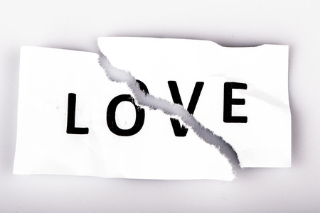 teared: Love word written on torn paper on white Stock Photo
