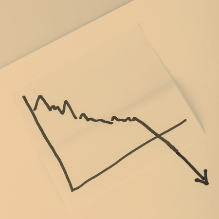 close up of a note paper with finance business graph going down