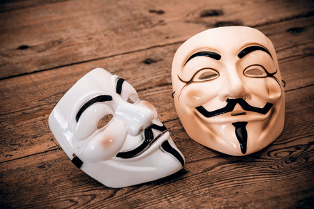 guy fawkes mask: white and yellow anonymous masks on wood background - retro style Stock Photo